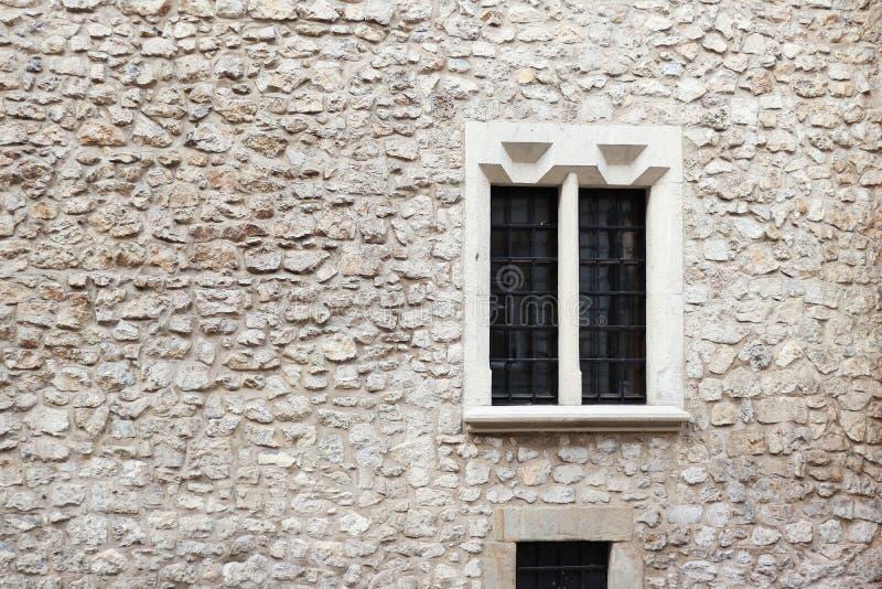 Pared de piedra y cemento viejos con la ventana vieja Fondo de piedra Pared de piedra de Kraków Planchas en las ventanas Edificio fotografía de archivo