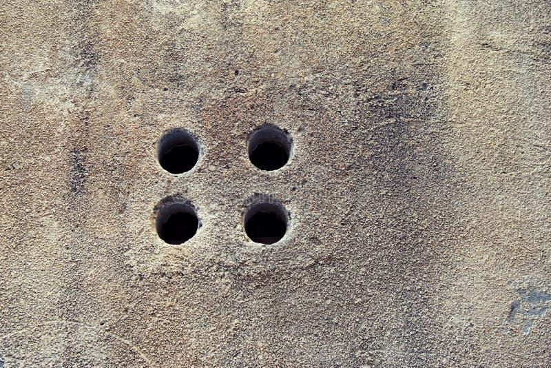 Pared de piedra y ventana con los agujeros en ciudad vieja foto de archivo