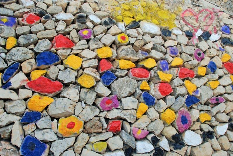 Pared de piedras coloreada que sorprende: azul, amarillo, rojo, negro, gris, violeta imagenes de archivo