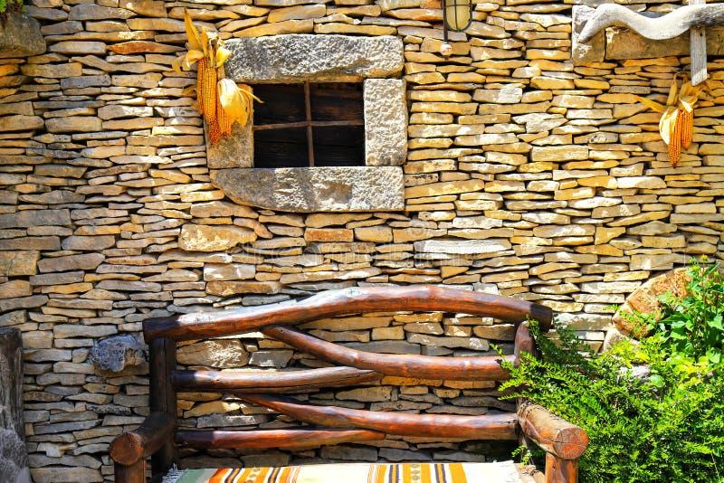 Pared de una casa rural del otoño con una pequeña ventana, un banco de madera Casa del pueblo en caída de la hoja fotografía de archivo