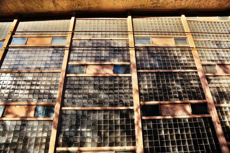 Pared del edificio viejo hecha de muchos pedazos de cristal en los rayos del sol imagen de archivo libre de regalías