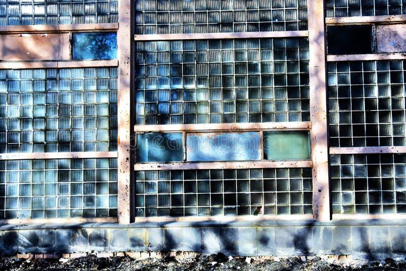 Pared del edificio viejo hecha de muchos pedazos de cristal en los rayos del sol fotos de archivo libres de regalías
