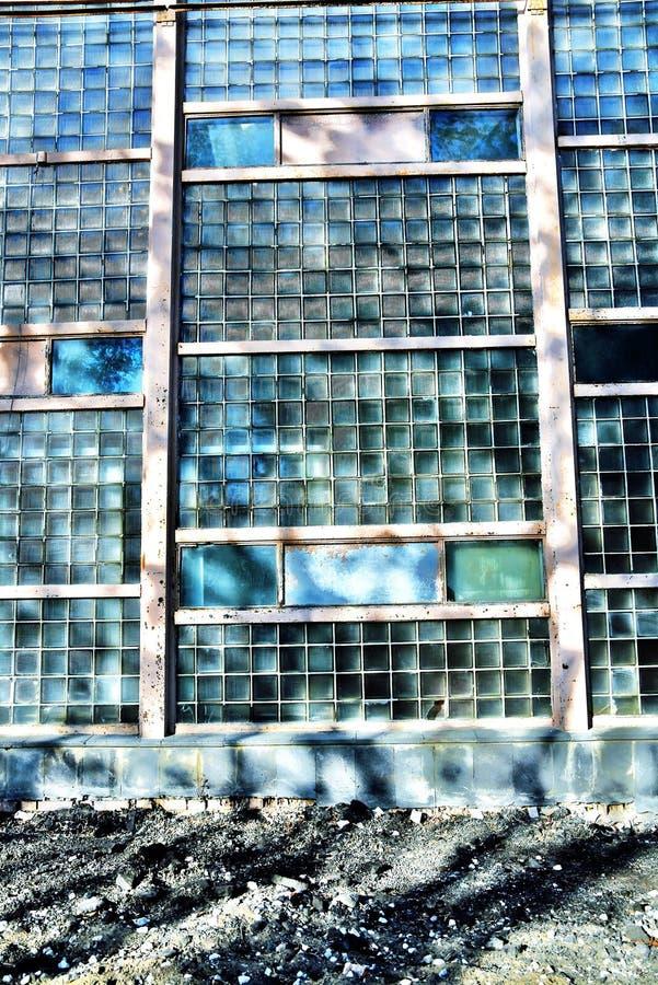 Pared del edificio viejo hecha de muchos pedazos de cristal en los rayos del sol foto de archivo libre de regalías