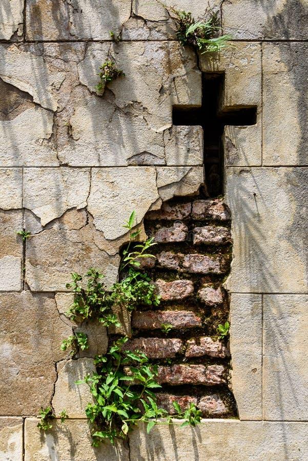 Pared del mausoleo que desmenuza con un corte cruzado en ?l y plantas que crecen fuera de la pared, de la piedra y del ladrillo fotos de archivo libres de regalías