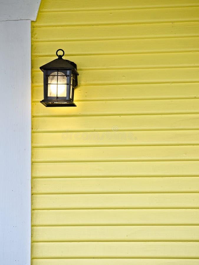 Pared exterior amarilla con la lámpara en un edificio viejo imágenes de archivo libres de regalías