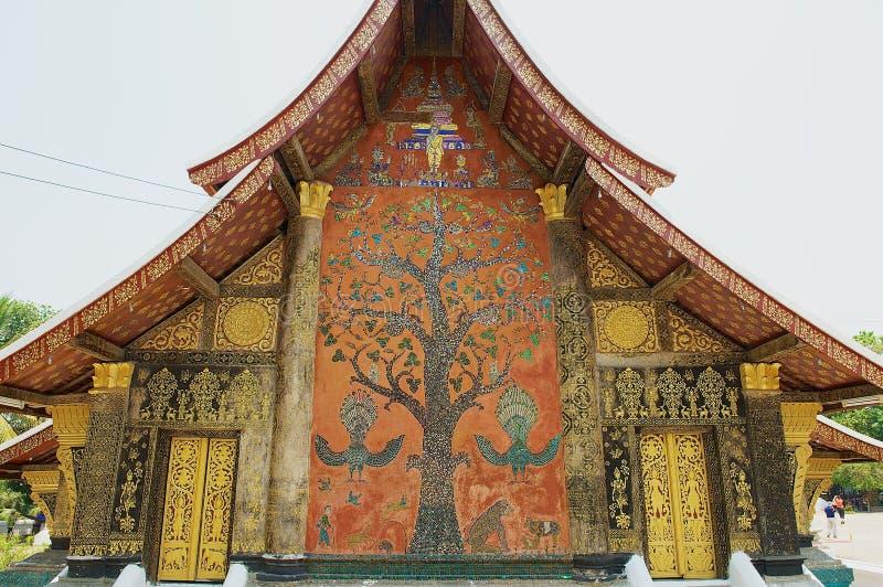 Pared exterior con el mosaico hermoso del árbol del pabellón en el templo de la correa de Xieng en Luang Prabang, Laos imagen de archivo libre de regalías
