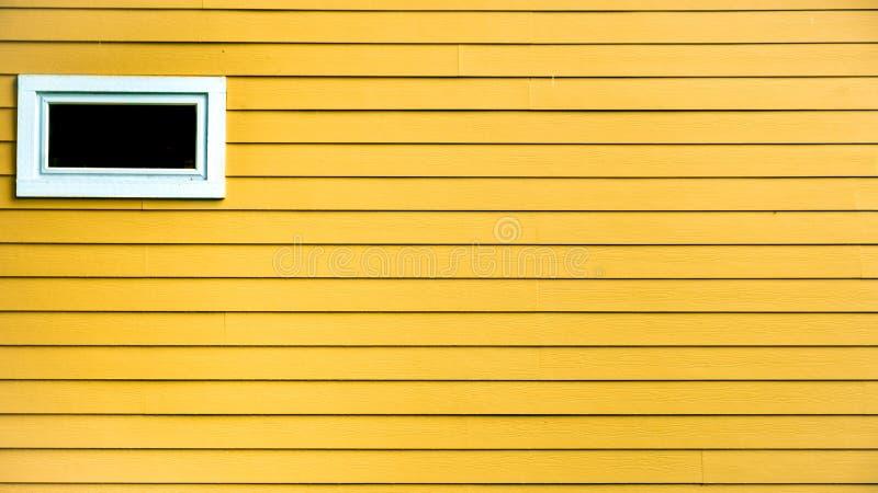 Pared exterior de la casa hecha de los tablones de madera con el pequeño espacio de la ventana y de la copia imagenes de archivo