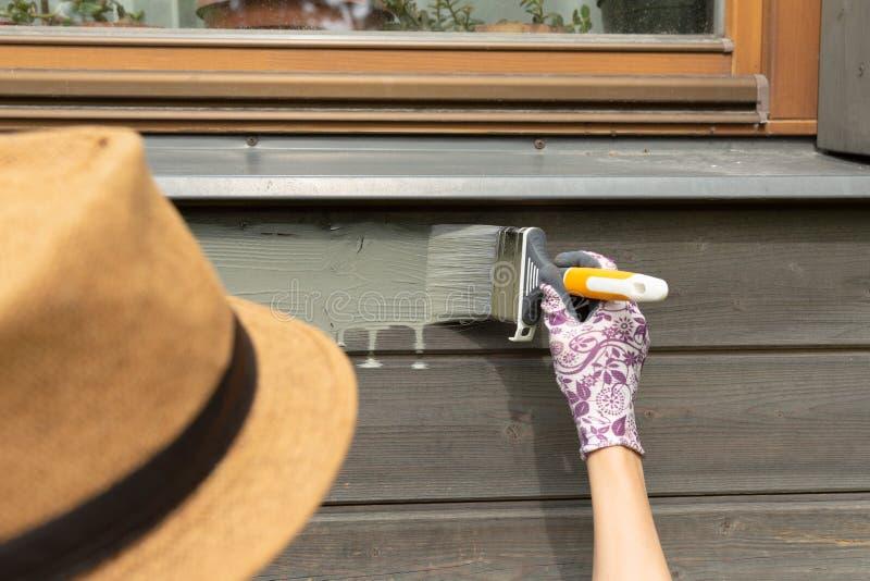 Pared exterior de la casa de madera de la pintura del trabajador de mujer con la brocha y el color protector de madera fotografía de archivo libre de regalías
