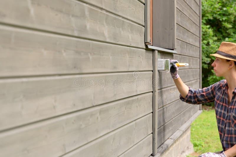 Pared exterior de la casa de madera de la pintura del trabajador de mujer con la brocha y el color protector de madera imagen de archivo libre de regalías
