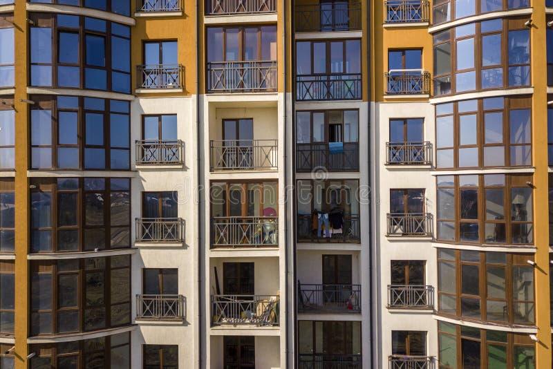 Pared exterior del detalle del apartamento o del edificio de oficinas La verja forjada del balcón, cielo azul reflejó en ventanas imágenes de archivo libres de regalías