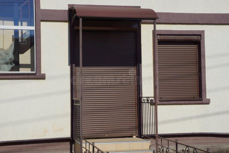 Pared gris de la casa con una ventana y una puerta cubiertas con las persianas de rodillo marrones fotografía de archivo libre de regalías