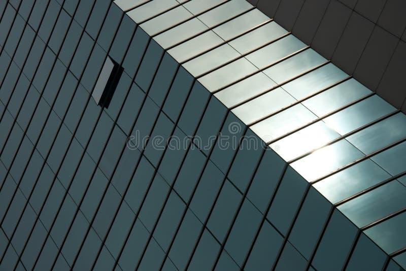 Pared iluminada por el sol verde angulosa del rascacielos de cristal foto de archivo