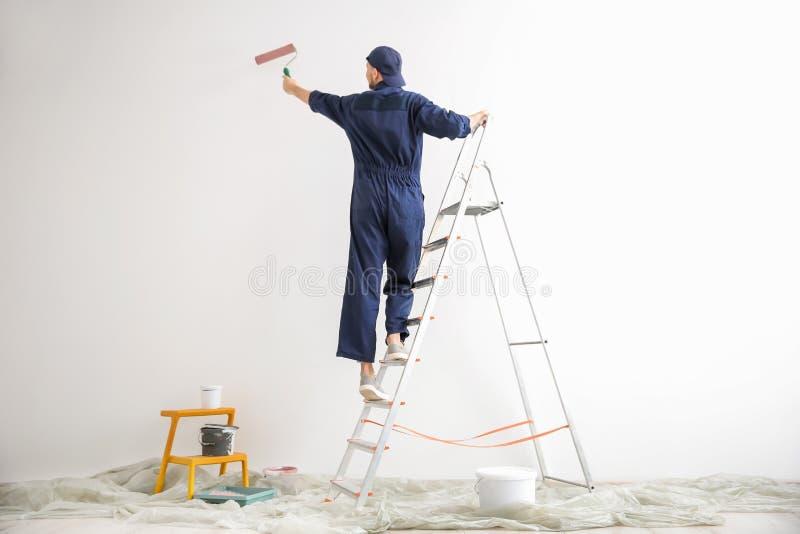 Pared masculina joven de la pintura del decorador imagen de archivo libre de regalías