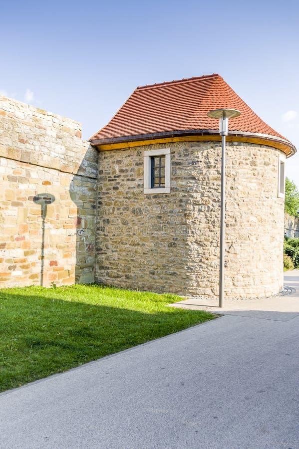 Pared medieval de la ciudad con la torre fortificada y parque adyacente en imagen de archivo libre de regalías