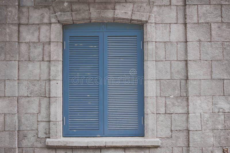Pared pedregosa de la casa con la ventana azul imagen de archivo
