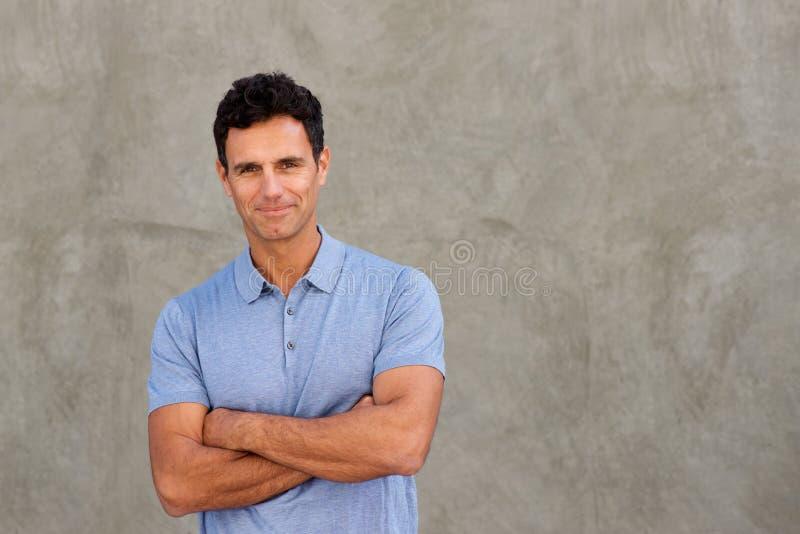 Pared que hace una pausa del hombre hermoso con los brazos cruzados foto de archivo libre de regalías