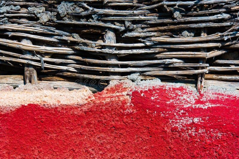 Pared roja con la cerca de mimbre con el suelo imagenes de archivo