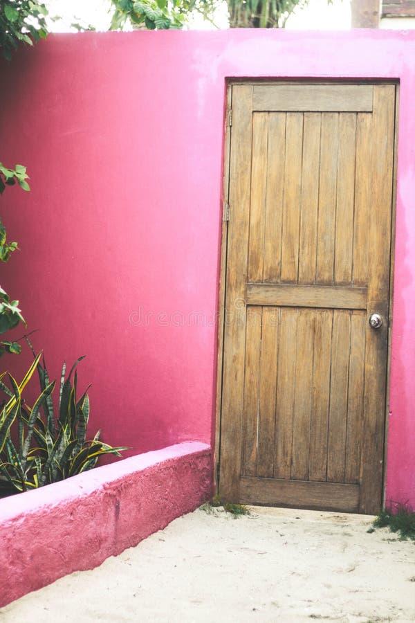 Pared rosada con la puerta de madera imagenes de archivo