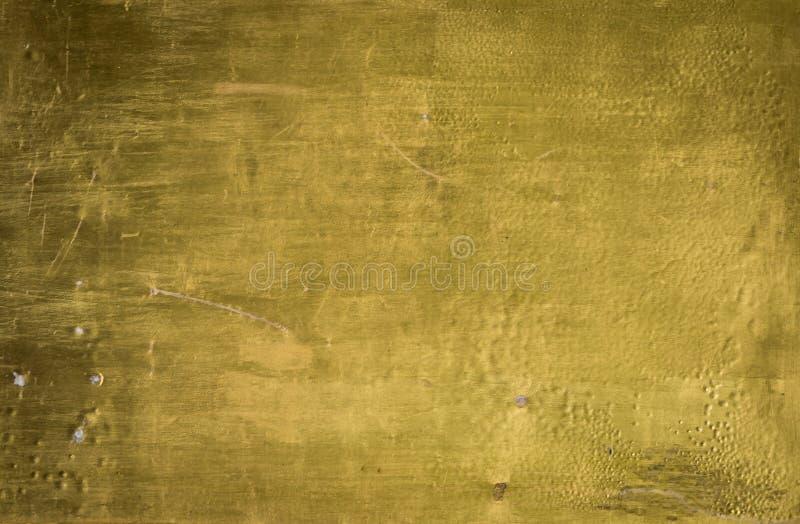 Pared sucia pintada en textura del color oro fotos de archivo