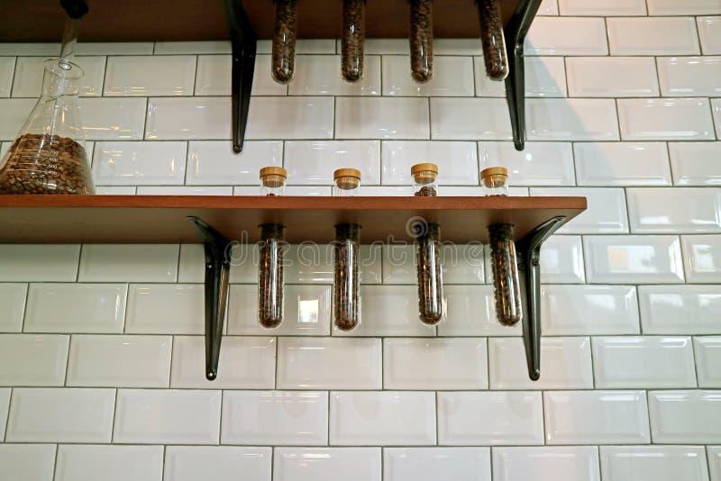 Pared tejada blanca con el café Bean Storage Glass Tubes Shelf fotografía de archivo