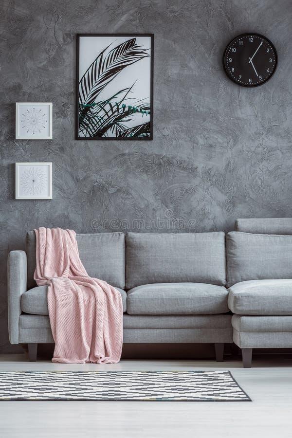 Pared texturizada hormigón, sofá gris imagen de archivo libre de regalías