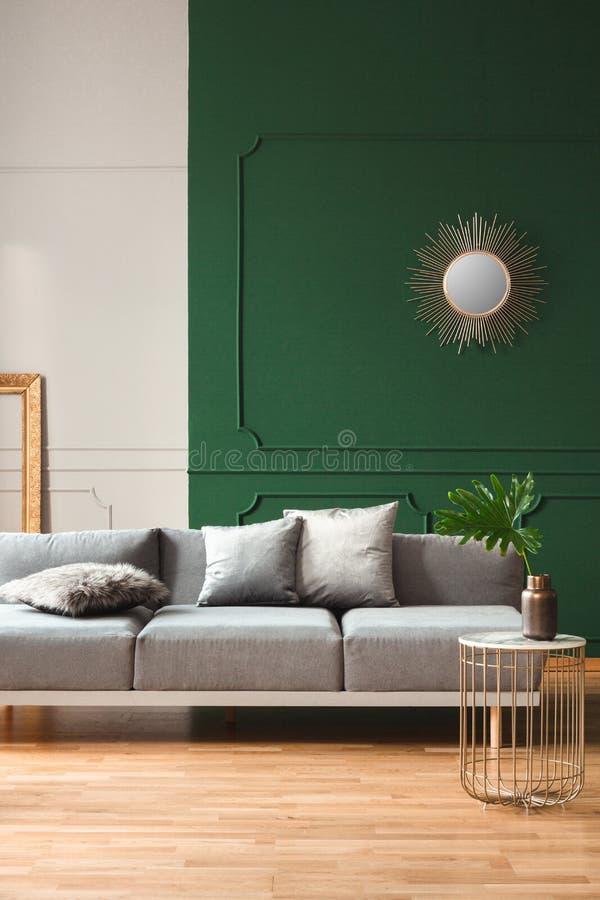 Pared verde y gris con el moldeado en la sala de estar elegante interior con el sof? gris y el piso de madera imagen de archivo