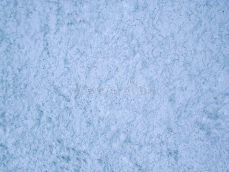 Parede áspera do cimento Craggy na luz ártica - fundo azul imagem de stock