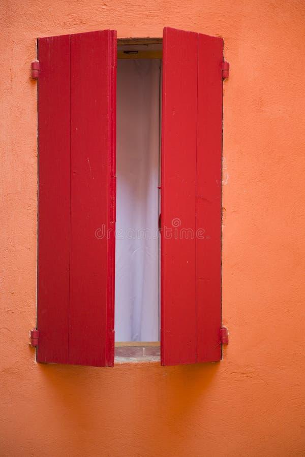 Parede alaranjada, obturador vermelho da janela fotos de stock royalty free