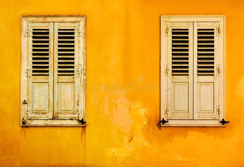 Parede amarela com duas janelas foto de stock royalty free