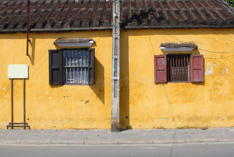 Parede amarela suja, janela do ferro forjado dos obturadores, Hoi An, Vietname fotografia de stock