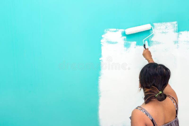 Parede asiática unidentifiable nova da pintura da mulher com rolo de pintura imagens de stock royalty free