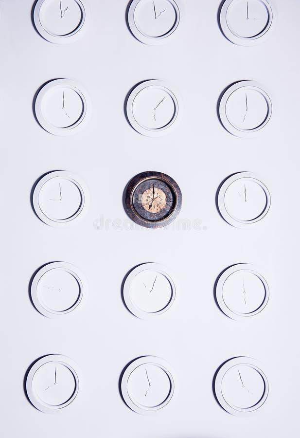 Parede branca com os pulsos de disparo não numerais redondos idênticos do branco e o um pulso de disparo escuro original Fundo do fotografia de stock royalty free