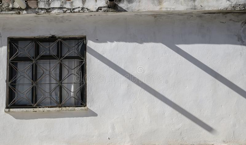 A parede branca da casa, uma janela na parede, duas sombras paralelas cria um ritmo na foto, imagem de stock