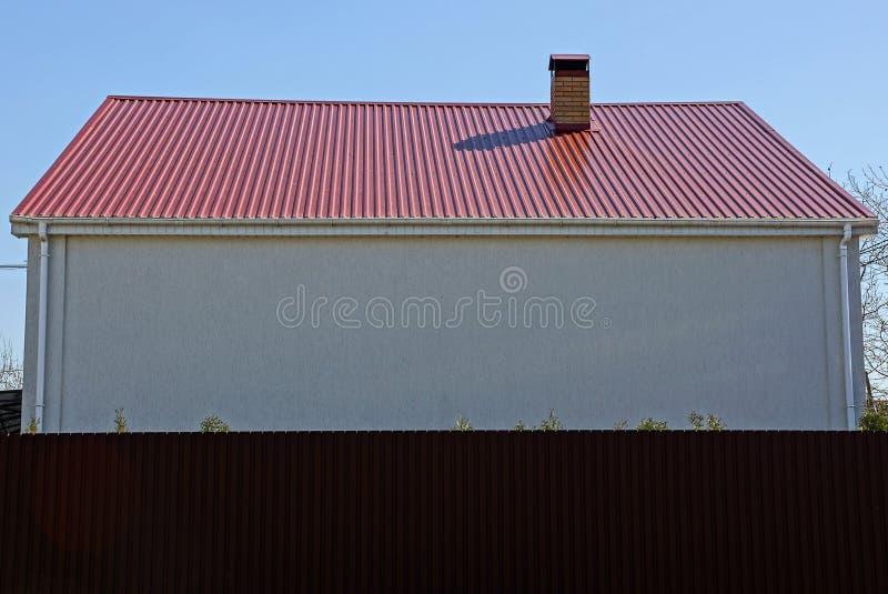 Parede branca de uma casa com um telhado vermelho atrás de uma cerca marrom fotos de stock