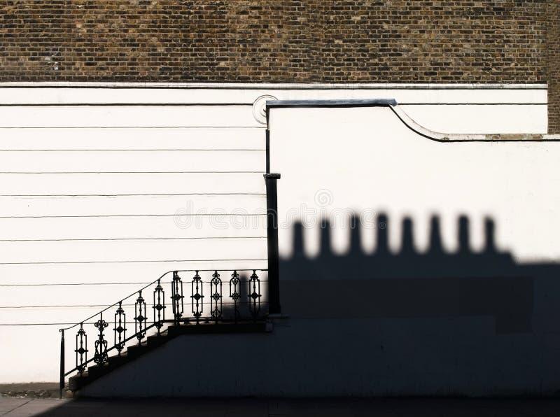 Parede branca do emplastro, parede de tijolo e etapas com o corrimão decorativo do ferro Sombra de telhado vizinho com as chaminé fotografia de stock