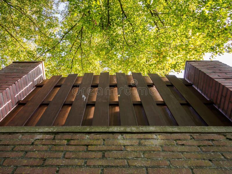 Parede, cerca e árvores de tijolo foto de stock royalty free