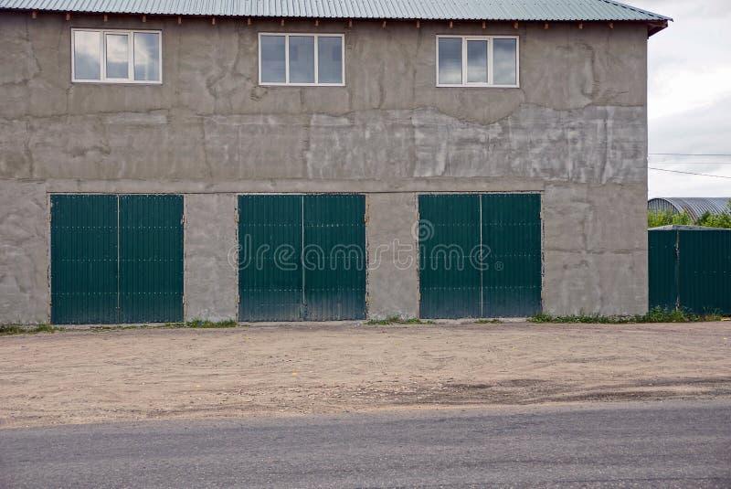 A parede cinzenta de uma grande casa com janelas e três passam portas da garagem na rua foto de stock