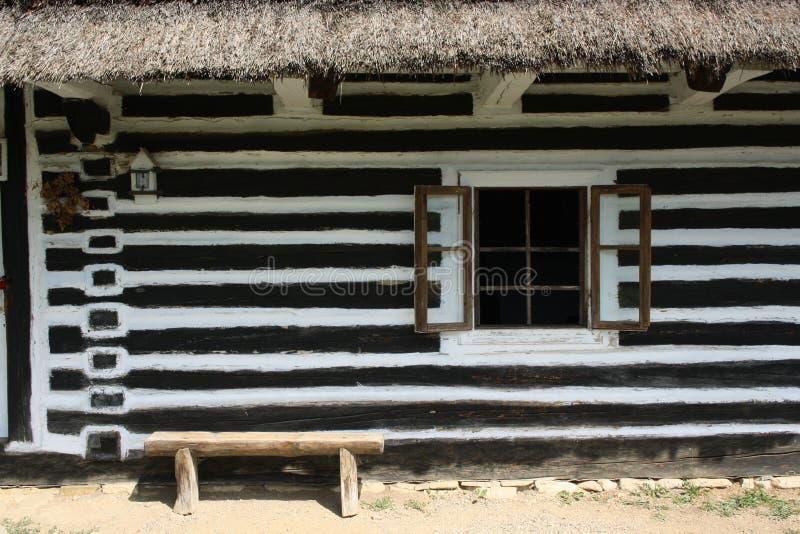 Parede com uma janela da casa de madeira pintada nas listras imagens de stock royalty free