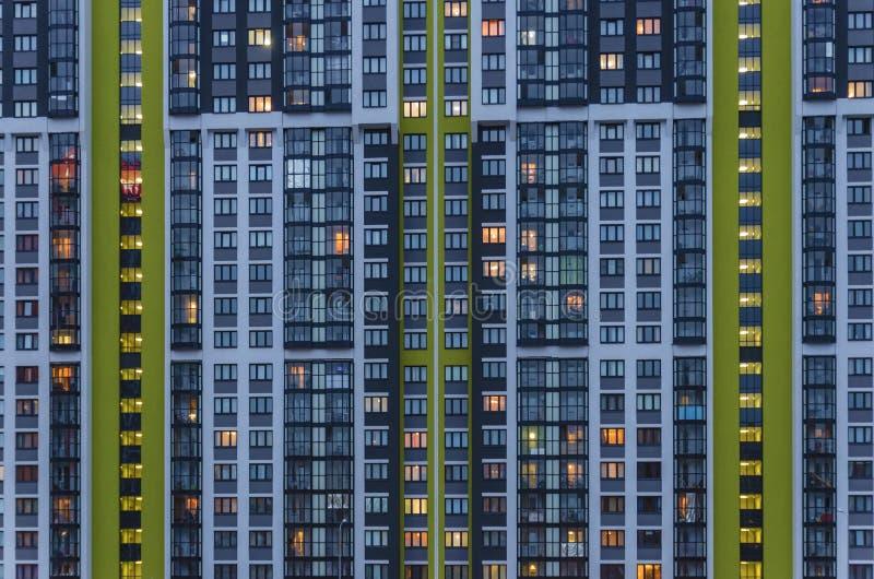 Parede da casa com luzes em Windows, o conceito da superpopulação das cidades, grandes casas como formigueiros foto de stock