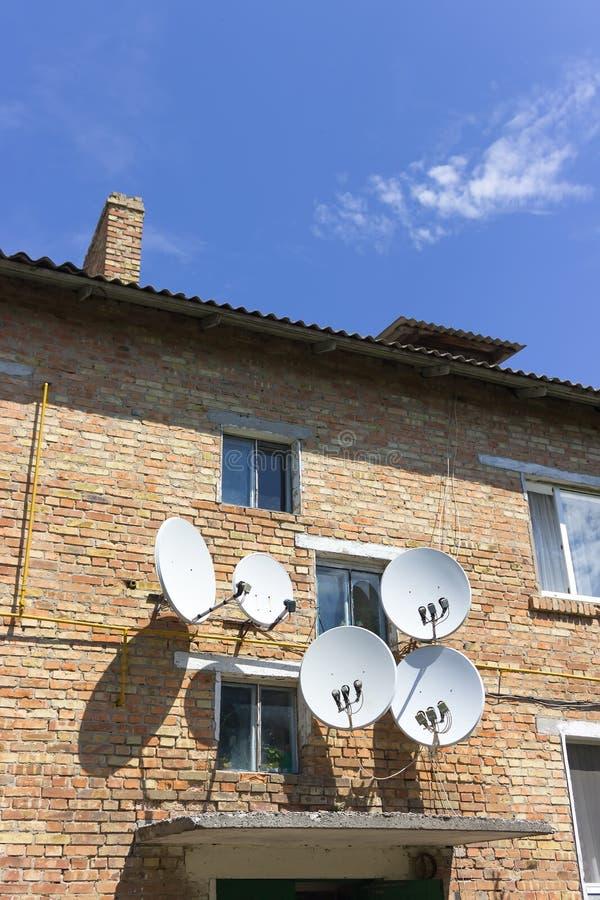 Parede da casa do tijolo vermelho com as antenas da placa da antena parabólica fotografia de stock