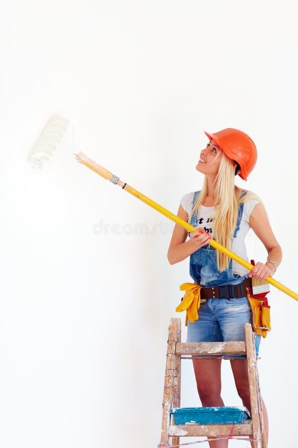 Parede da coloração da moça com rolo, ao estar na escada fotos de stock