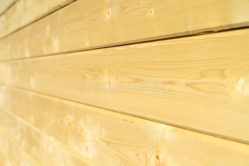 Parede da foto de uma casa de madeira feita de feixes de madeira fotografia de stock royalty free