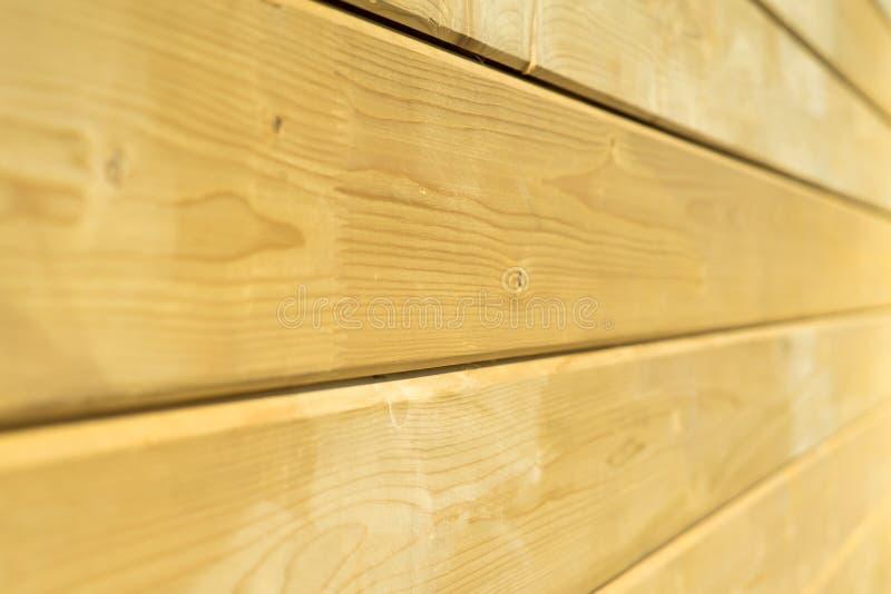 Parede da foto de uma casa de madeira feita de feixes de madeira fotos de stock