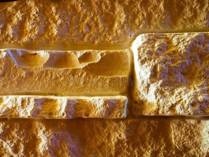 Parede da pedra decorativa clara sob a rocha com saliências e sombras imagens de stock