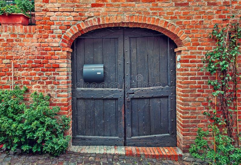 Parede da porta de madeira e de tijolo vermelho fotos de stock