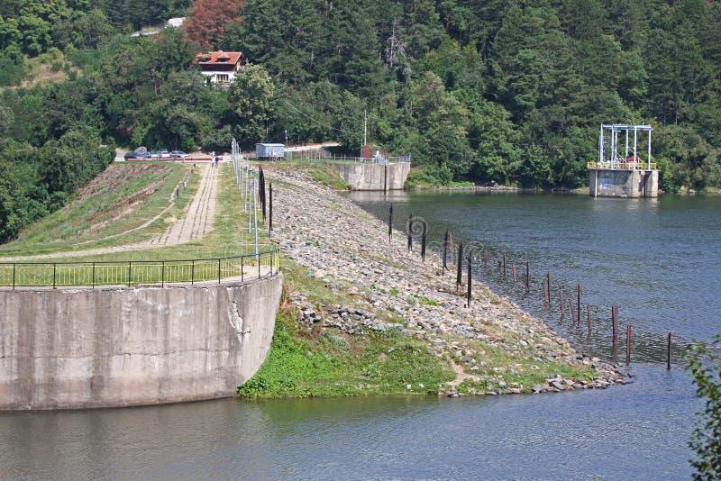 Parede da represa e excesso da represa de Iskar Água que flui sobre uma parede da represa Névoa que aumenta acima da parede da re imagens de stock