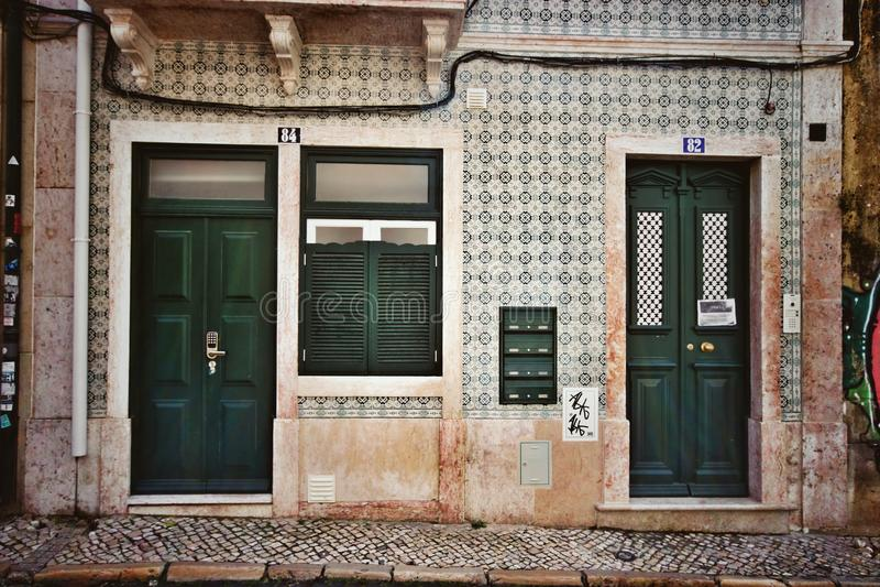 Parede da telha com as portas verdes em Lisboa fotografia de stock