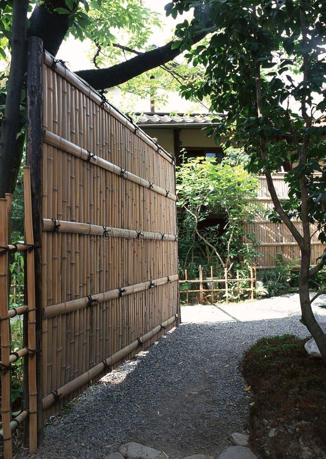 Parede de bambu japonesa no jardim exterior com árvores e plantas fotografia de stock