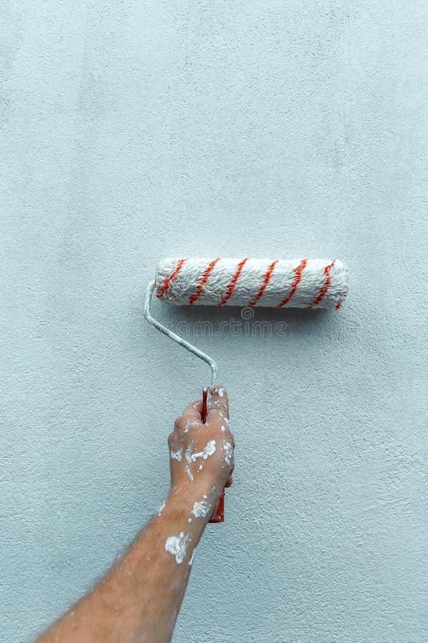 Parede de Hand Paints The do pintor com rolo de pintura, close-up com Co fotos de stock royalty free