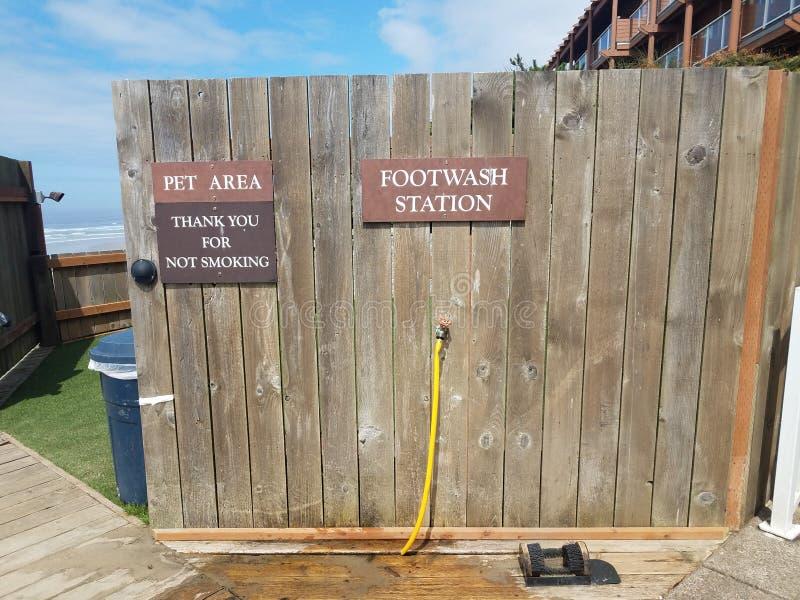 A parede de madeira com área do animal de estimação da estação do footwash agradece-lhe para sinais de fumo na praia imagem de stock royalty free
